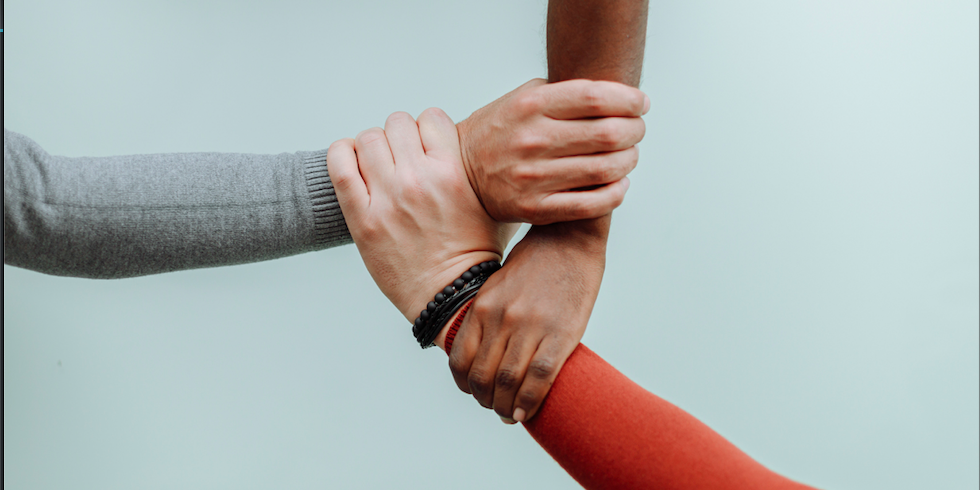 Personnes se tenant les poignets en signe de collaboration et de solidarité